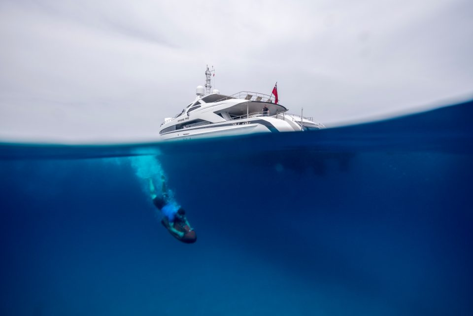 A man dives beneath the Amore Mio yacht
