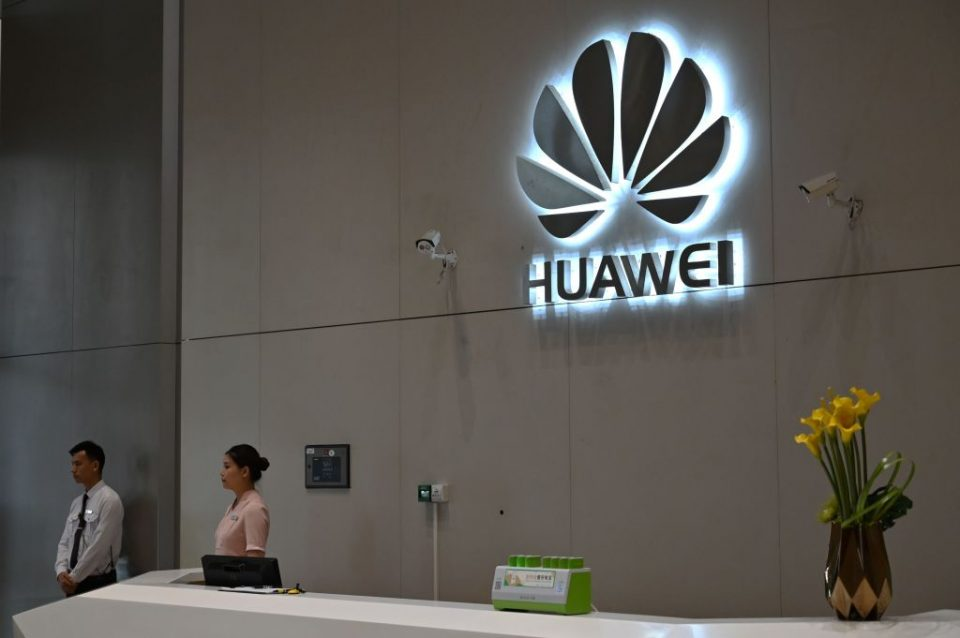 """In this picture taken on May 29, 2019, a company logo is displayed at a reception area at the Huawei headquarters in Shenzhen, China's Guangdong province. - Huawei's main Shenzhen campus is a sprawling, lavishly landscaped mix of glass office towers, labs and training centres, including a white-columned neo-classical research site the size of a city block and cheekily dubbed the """"White House"""" for its resemblance to US President Donald Trump's current address. (Photo by HECTOR RETAMAL / AFP) / To go with China-US-trade-Huawei-telecommunication, SCENE by Dan Martin (Photo credit should read HECTOR RETAMAL/AFP/Getty Images)"""