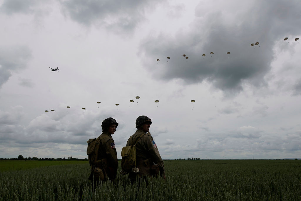 SANNERVILLE, FRANCE - JUNE 05: Performers look on as 280 paratroopers take part in a parachute drop onto fields at Sannerville on June 05, 2019 at Sannerville, France. Veterans, families, visitors and military personnel are gathering in Normandy on June 6th to commemorate the 75th anniversary of the Normandy Landings which heralded the Allied advance towards Germany and victory in Europe 11 months later. (Photo by Christopher Furlong/Getty Images)