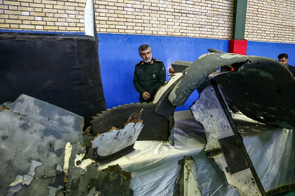 General Amir Ali Hajizadeh (C), Iran's Head of the Revolutionary Guard's aerospace division, looks at debris from a downed US drone reportedly recovered within Iran's territorial waters and put on display by the Revolutionary Guard in the capital Tehran on June 21, 2019. - Iran's state television broadcast images of what it said was debris from a downed US drone recovered inside its territorial waters. The television broadcast a short clip of a Revolutionary Guards general answering questions in front of some of the debris he said had been recovered after yesterday's missile strike. The downing of the drone -- which Washington insists was over international waters but Tehran says was within its airspace -- has seen tensions between the two countries spike further after a series of attacks on tankers the US has blamed on Iran. (Photo by Meghdad Madadi / TASNIM NEWS / AFP) (Photo credit should read MEGHDAD MADADI/AFP/Getty Images)