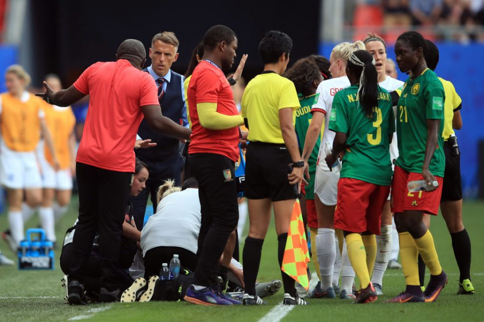 VALENCIENNES, FRANCE - JUNE 23: England Head Coach Phil Neville looks on as Cameroon Head Coach Alain Djeumfa reacts toward him late in the game during the 2019 FIFA Women's World Cup France Round Of 16 match between England and Cameroon at Stade du Hainaut on June 23, 2019 in Valenciennes, France. (Photo by Marc Atkins/Getty Images)