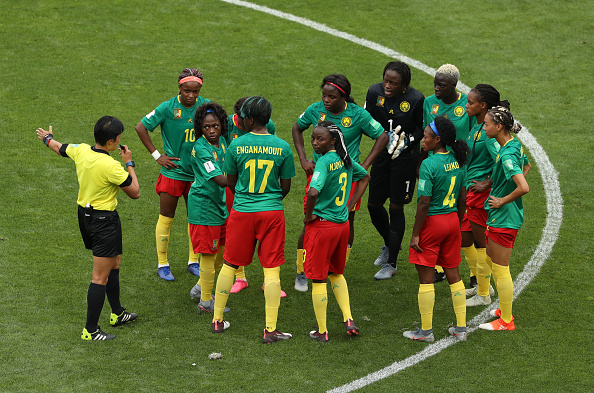 VALENCIENNES, FRANCE - JUNE 23: Players of Cameroon argue with referee Qin Liang following England's second goal during the 2019 FIFA Women's World Cup France Round Of 16 match between England and Cameroon at Stade du Hainaut on June 23, 2019 in Valenciennes, France. (Photo by Robert Cianflone/Getty Images)