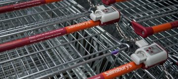 The logos of supermarket chain Sainsbury's are pictured on the handles of shopping trolleys outside a store in Stockport, northern England on April 30, 2018. - Britain's second and third biggest supermarket chains Sainsbury's and Walmart-owned Asda have agreed to merge, the pair said Monday, hoping to create a £13-billion ($18-billion, 15-billion-euro) retail king and leapfrog UK number one Tesco. The blockbuster deal -- which is effectively a takeover bid with Sainsbury's acquiring a majority 58-percent stake -- comes as the British supermarket sector faces squeezed profit margins and fierce competition from German-owned discounters Aldi and Lidl and online US titan Amazon. (Photo by OLI SCARFF / AFP) (Photo credit should read OLI SCARFF/AFP/Getty Images)