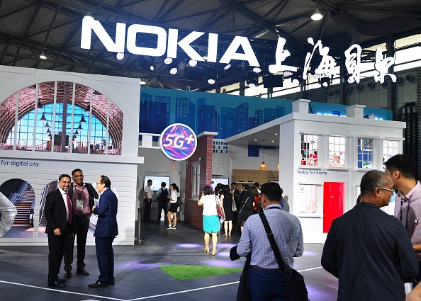 This photo taken on June 27, 2018 shows people gathering at a Nokia booth during the Mobile World Conference in Shanghai. (Photo by - / AFP) / China OUT (Photo credit should read -/AFP/Getty Images)