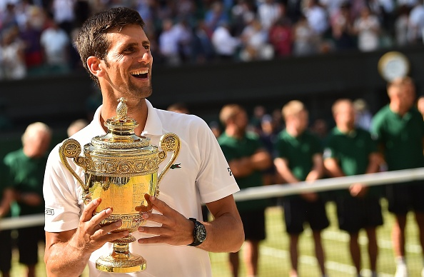 Serbia's Novak Djokovic holds the winners trophy after beating South Africa's Kevin Anderson 6-2, 6-2, 7-6 in their men's singles final match on the thirteenth day of the 2018 Wimbledon Championships at The All England Lawn Tennis Club in Wimbledon, southwest London, on July 15, 2018. (Photo by Glyn KIRK / AFP) / RESTRICTED TO EDITORIAL USE (Photo credit should read GLYN KIRK/AFP/Getty Images)
