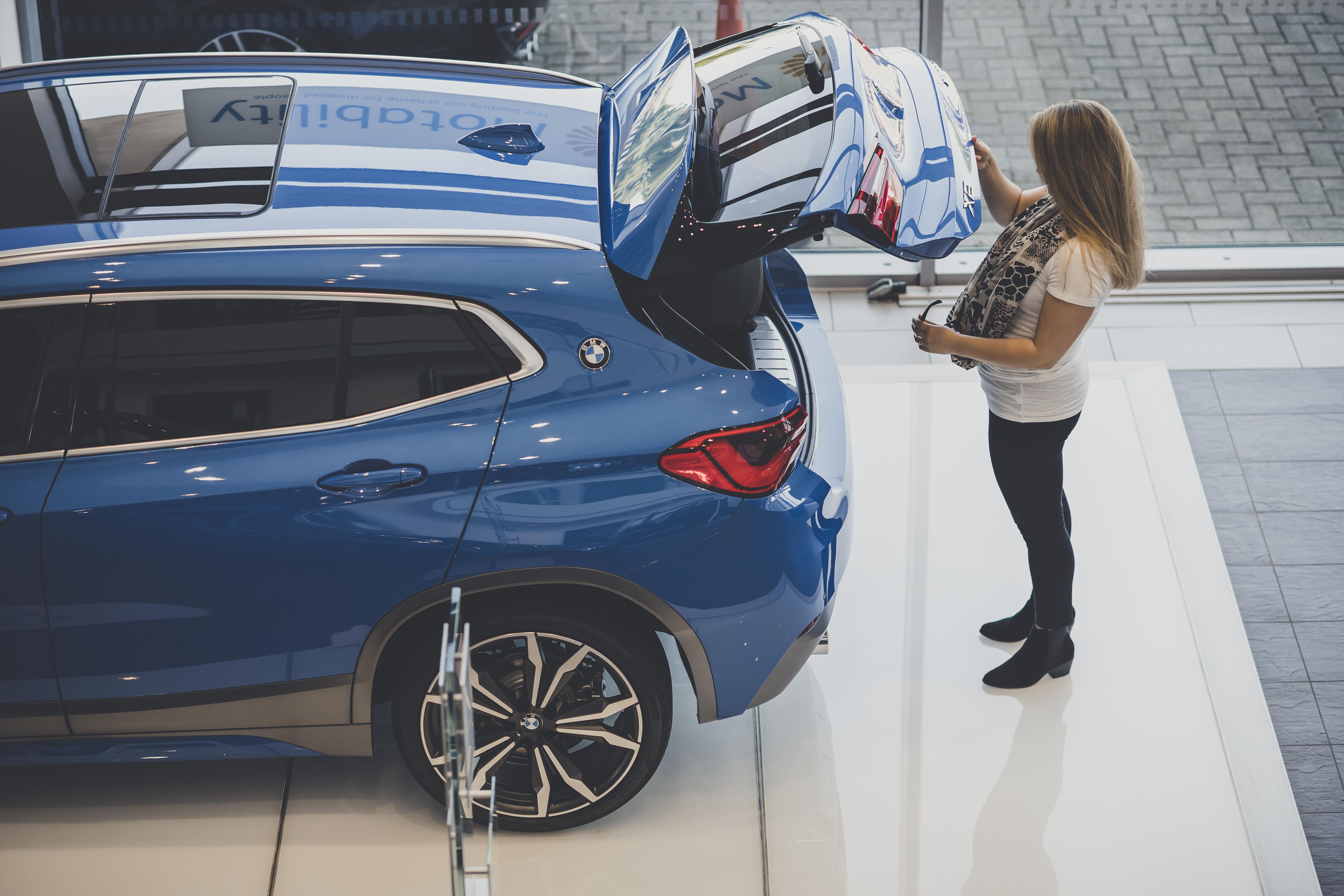 A women surveys a car at an Auto Trader show room