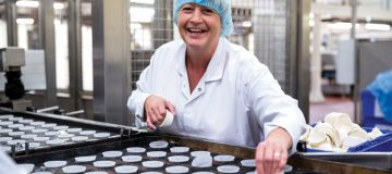 A Finsbury Food worker laughs as they prepare cupcakes in a factory (Main image credit: Finsbury Food)