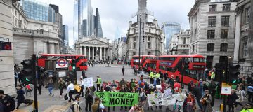 """LONDON, ENGLAND - APRIL 25: Envrionmental campaigners from the """"Extinction Rebellion"""" group block the junction at Bank as part of their ongoing actions and protests across the capital on April 25, 2019 in London, England. Organisers have said demonstrators will target the financial industry as it is due to end blockades at Parliament Square and Marble Arch on the eleventh and final day. The protests have involved roadblocks, sit-ins and the halting of sections of the public transport system, in a bid to highlight environmental concerns. (Photo by Leon Neal/Getty Images)"""