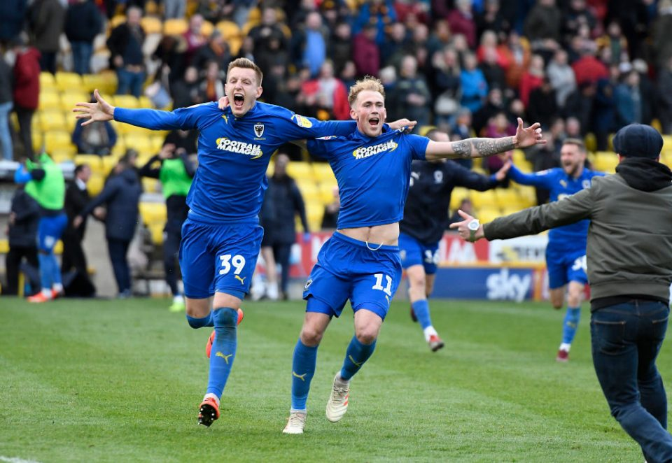 BRADFORD, ENGLAND - MAY 04: Joe Piggott and Mitchell Pinnock of AFC Wimbledon celebrate with fans after the 0-0 with Bradford results in AFC Wimbledon staying up in League One following the Sky Bet League One match between Bradford City and AFC Wimbledon at Northern Commercials Stadium on May 04, 2019 in Bradford, United Kingdom. (Photo by George Wood/Getty Images)