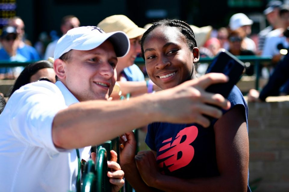 "US player Cori Gauff (R) poses for a selfie with fans after a session on the practice courts at The All England Tennis Club in Wimbledon, southwest London, on July 4, 2019, on the fourth day of the 2019 Wimbledon Championships tennis tournament. - Coco Gauff, the 15-year-old schoolgirl who stunned five-time champion Venus Williams in the first round, continued her Wimbledon dream debut on Wednesday when she eased into the last 32 and claimed: ""I can beat anyone."" Next up for Gauff is a last 32 clash against world number 60 Polona Hercog of Slovenia on July 5. (Photo by Daniel LEAL-OLIVAS / AFP) / RESTRICTED TO EDITORIAL USE        (Photo credit should read DANIEL LEAL-OLIVAS/AFP/Getty Images)"