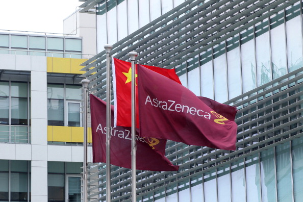 Company flags fly next to the Chinese one outside the headquarters of Britain's AstraZenica China headquarters in the Zhangjiang district of Shanghai on July 24, 2013. Beijing's targeting of British pharmaceutical giant GlaxoSmithKline (GSK) in a high-profile bribery probe is a reminder of the risks foreign companies face when seeking the huge rewards of China's market, analysts say. Police say GSK staff offered government officials and doctors bribes, and took kick-backs from travel agencies to organise conferences, some of which were fake. Chinese authorities have also questioned three Shanghai-based employees of Britain's AstraZeneca, detaining two, and have visited the offices of Belgium's UCB, according to the companies, although they did not specify what was being investigated. CHINA OUT AFP PHOTO (Photo credit should read STR/AFP/Getty Images)