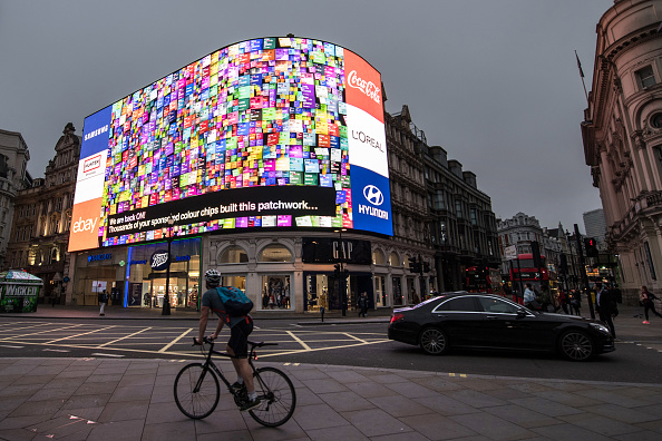 LONDON, ENGLAND - OCTOBER 26: Members of the public watch as an animation is seen after the countdown as the Piccadilly Circus lights are switched back on after a nine month renovation on October 26, 2017 in London, England. The new Piccadilly Circus lights advertising boards replace a patchwork of screens with a single 4K LED digital screen, the largest of its kind in Europe. (Photo by Chris J Ratcliffe/Getty Images)