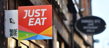 A sign for Just Eat, a food delivery service can be seen above a restaurant in London on December 18, 2017. Just Eat has been welcomed on December 18, 2017 into UK's FTSE 100 index of the country's largest publicly listed companies. / AFP PHOTO / BEN STANSALL (Photo credit should read BEN STANSALL/AFP/Getty Images)
