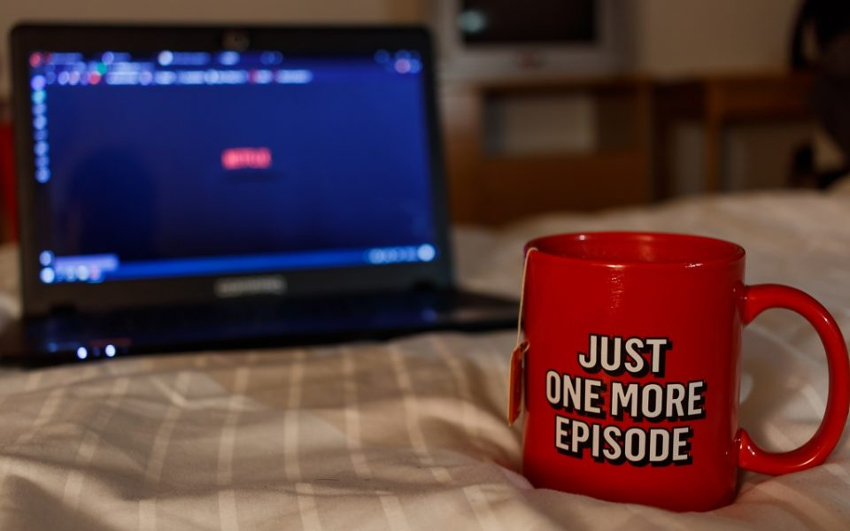 Tea cup and laptop on bed watching Netflix