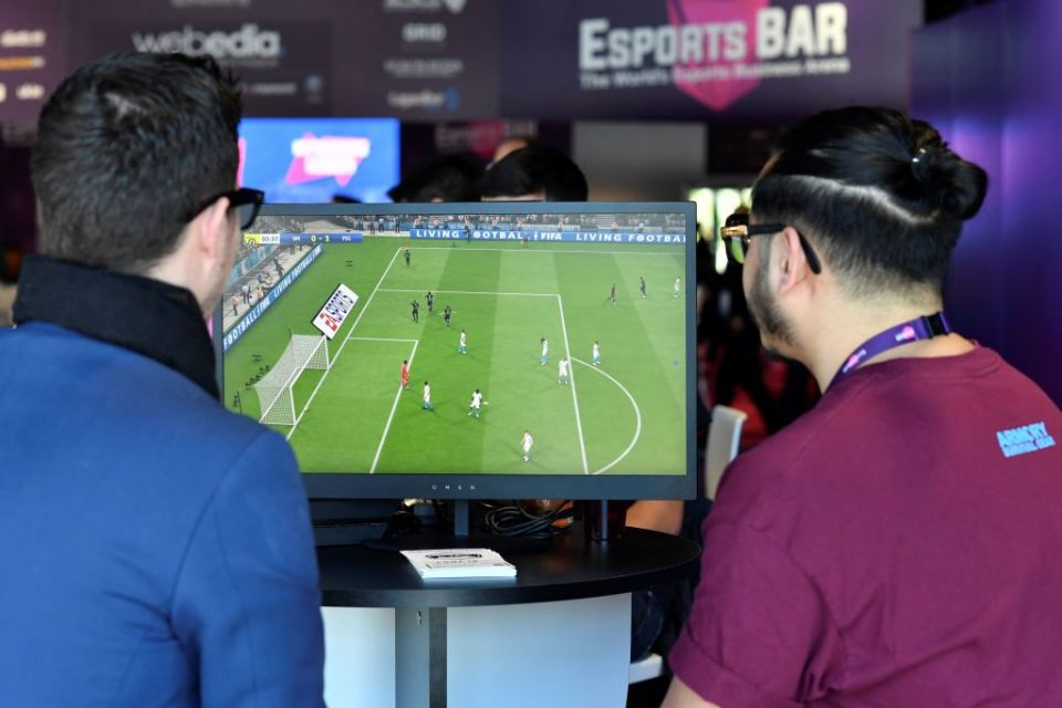 "Visitors plays on EA Vancouver video game developer's football simulation video game FIFA 19 at the eSports Bar trade fair in Cannes, southern France on February 13, 2019. - After several years of development under radars, eSports is attracting more and more major brands that are betting on this sector in ""structuring phase"" to communicate with a different but committed target, according to Stephane Gambetta, director of activities and strategy at Reed Midem, the organizer of the eSports Bar trade fair in Cannes. (Photo by YANN COATSALIOU / AFP)        (Photo credit should read YANN COATSALIOU/AFP/Getty Images)"