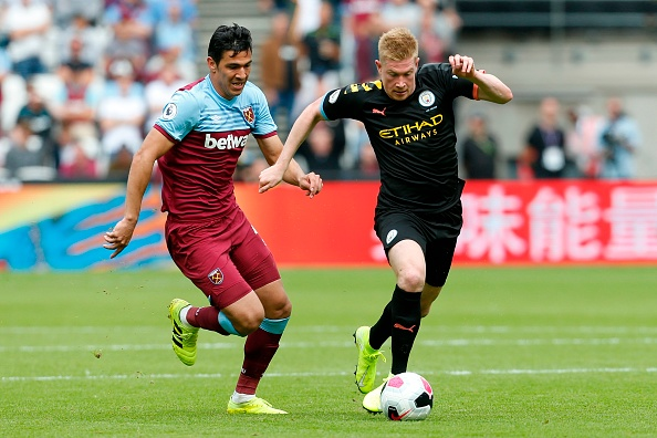 West Ham United's Paraguayan defender Fabián Balbuena (L) chases Manchester City's Belgian midfielder Kevin De Bruyne (R) during the English Premier League football match between West Ham United and Manchester City at The London Stadium, in east London on August 10, 2019. (Photo by Ian KINGTON / AFP) / RESTRICTED TO EDITORIAL USE. No use with unauthorized audio, video, data, fixture lists, club/league logos or 'live' services. Online in-match use limited to 120 images. An additional 40 images may be used in extra time. No video emulation. Social media in-match use limited to 120 images. An additional 40 images may be used in extra time. No use in betting publications, games or single club/league/player publications. /         (Photo credit should read IAN KINGTON/AFP/Getty Images)