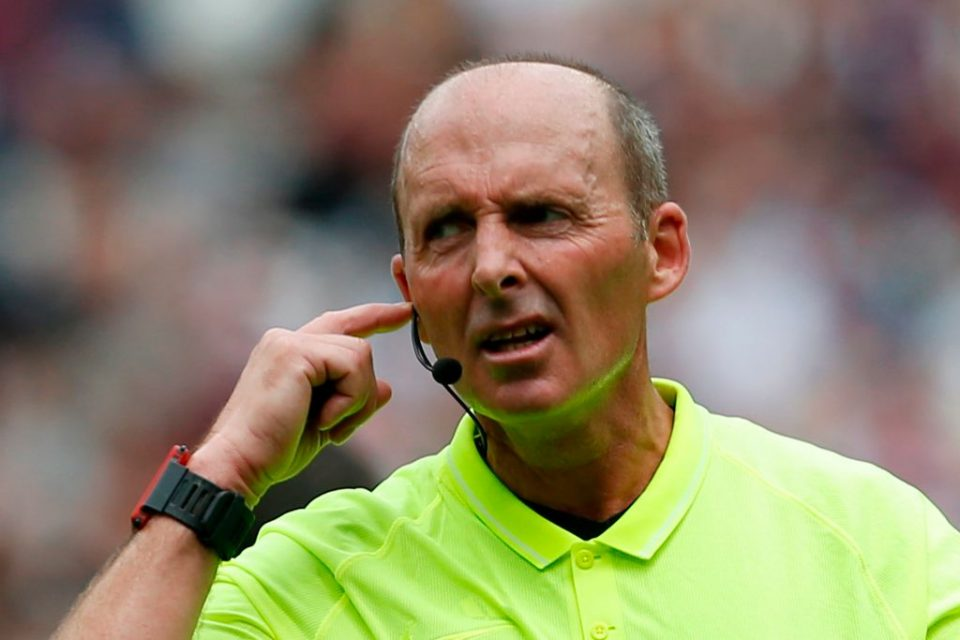 Referee Mike Dean communicates with the VAR (video assistant referee) as a Manchester City penalty, which was saved, is being checked and ruled that it must be retaken during the English Premier League football match between West Ham United and Manchester City at The London Stadium, in east London on August 10, 2019. (Photo by Ian KINGTON / AFP) / RESTRICTED TO EDITORIAL USE. No use with unauthorized audio, video, data, fixture lists, club/league logos or 'live' services. Online in-match use limited to 120 images. An additional 40 images may be used in extra time. No video emulation. Social media in-match use limited to 120 images. An additional 40 images may be used in extra time. No use in betting publications, games or single club/league/player publications. /         (Photo credit should read IAN KINGTON/AFP/Getty Images)