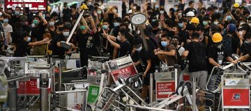 "Pro-democracy protestors block the entrance to the airport terminals after a scuffle with police at Hong Kong's international airport on August 13, 2019. - Hundreds of flights were cancelled or suspended at Hong Kong's airport on August 13, 2019 as pro-democracy protesters staged a second disruptive sit-in at the sprawling complex, defying warnings from the city's leader who said they were heading down a ""path of no return"". The new protest came as Beijing sent further ominous signals that the 10 weeks of unrest must end, with state-run media showing videos of security forces gathering across the border. (Photo by Manan VATSYAYANA / AFP) (Photo credit should read MANAN VATSYAYANA/AFP/Getty Images)"