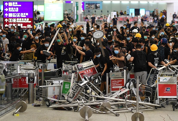 """Pro-democracy protestors block the entrance to the airport terminals after a scuffle with police at Hong Kong's international airport on August 13, 2019. - Hundreds of flights were cancelled or suspended at Hong Kong's airport on August 13, 2019 as pro-democracy protesters staged a second disruptive sit-in at the sprawling complex, defying warnings from the city's leader who said they were heading down a """"path of no return"""". The new protest came as Beijing sent further ominous signals that the 10 weeks of unrest must end, with state-run media showing videos of security forces gathering across the border. (Photo by Manan VATSYAYANA / AFP) (Photo credit should read MANAN VATSYAYANA/AFP/Getty Images)"""