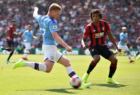 Manchester City's Belgian midfielder Kevin De Bruyne (L) crosses the ball past Bournemouth's Dutch defender Nathan Ake during the English Premier League football match between Bournemouth and Manchester City at the Vitality Stadium in Bournemouth, southern England on August 25, 2019. (Photo by Glyn KIRK / AFP) / RESTRICTED TO EDITORIAL USE. No use with unauthorized audio, video, data, fixture lists, club/league logos or 'live' services. Online in-match use limited to 120 images. An additional 40 images may be used in extra time. No video emulation. Social media in-match use limited to 120 images. An additional 40 images may be used in extra time. No use in betting publications, games or single club/league/player publications. /         (Photo credit should read GLYN KIRK/AFP/Getty Images)