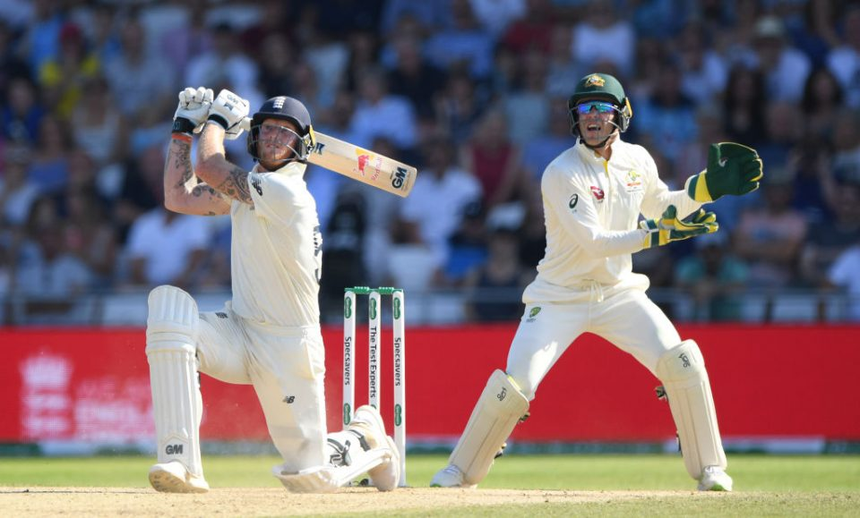 LEEDS, ENGLAND - AUGUST 25: England batsman Ben Stokes hits a ball for 6 runs watched by Tim Paine during day four of the 3rd Ashes Test Match between England and Australia at Headingley on August 25, 2019 in Leeds, England. (Photo by Stu Forster/Getty Images)