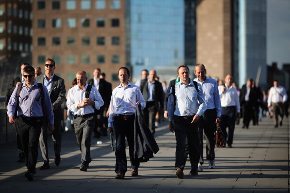LONDON, ENGLAND - JULY 17: City Workers walk along London Bridge in the early morning sunshine on July 17, 2014 in London, England. The Met Office has issued a heatwave alert as temperatures throughout England and Wales are predicted to reach their highest level of the year this weekend. (Photo by Dan Kitwood/Getty Images)