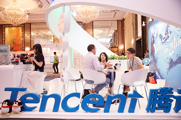 SINGAPORE - MARCH 15: Visitors and exhibitors network at the Tencent booth during the Sportel Asia Conference on March 15, 2016 in Singapore. (Photo by Sean Lee/Getty Images for Sportel)