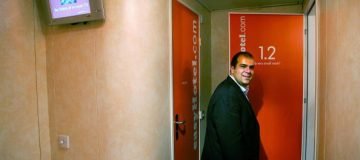 "London, UNITED KINGDOM: Entrepreneur Stelios Haji-Ioannou poses inside one of ""the very small rooms"" in his latest venture easyHotel in London 01 August 2005. EasyHotel represents the easyGroup entry into the budget hotel sector and will be found in the centre of international cities, targeting short-stay customers. The no-frills rooms in the west London hotel cost approzimately GBP20 (E30) but the price is on the basis of the earlier you book, the less you pay. AFP PHOTO ADRIAN DENNIS (Photo credit should read ADRIAN DENNIS/AFP/Getty Images)"