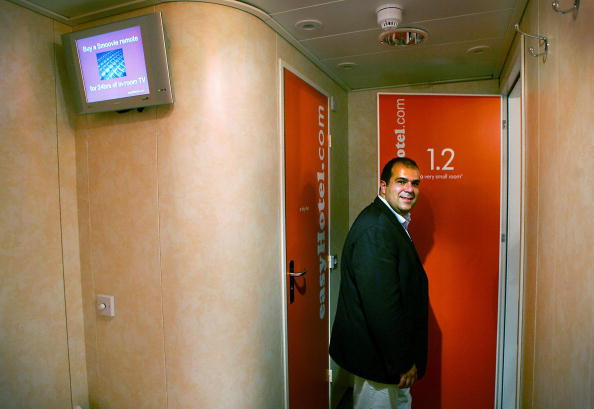 """London, UNITED KINGDOM: Entrepreneur Stelios Haji-Ioannou poses inside one of """"the very small rooms"""" in his latest venture easyHotel in London 01 August 2005. EasyHotel represents the easyGroup entry into the budget hotel sector and will be found in the centre of international cities, targeting short-stay customers. The no-frills rooms in the west London hotel cost approzimately GBP20 (E30) but the price is on the basis of the earlier you book, the less you pay. AFP PHOTO ADRIAN DENNIS (Photo credit should read ADRIAN DENNIS/AFP/Getty Images)"""