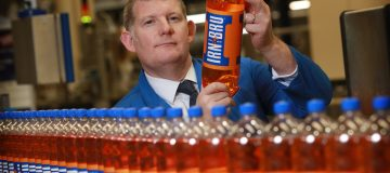 AG Barr CEO Roger White holds up a bottle of Irn-Bru from a factory line of its signature products