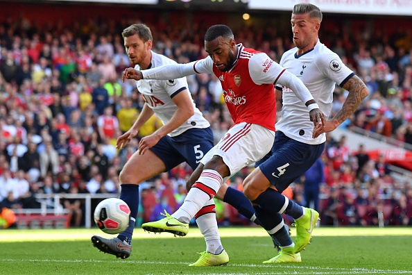 Arsenal's French striker Alexandre Lacazette shoots to score their first goal during the English Premier League football match between Arsenal and Tottenham Hotspur at the Emirates Stadium in London on September 1, 2019. (Photo by Ben STANSALL / AFP) / RESTRICTED TO EDITORIAL USE. No use with unauthorized audio, video, data, fixture lists, club/league logos or 'live' services. Online in-match use limited to 120 images. An additional 40 images may be used in extra time. No video emulation. Social media in-match use limited to 120 images. An additional 40 images may be used in extra time. No use in betting publications, games or single club/league/player publications. /         (Photo credit should read BEN STANSALL/AFP/Getty Images)
