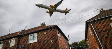 A Thomas Cook plane can be seen above a row of houses