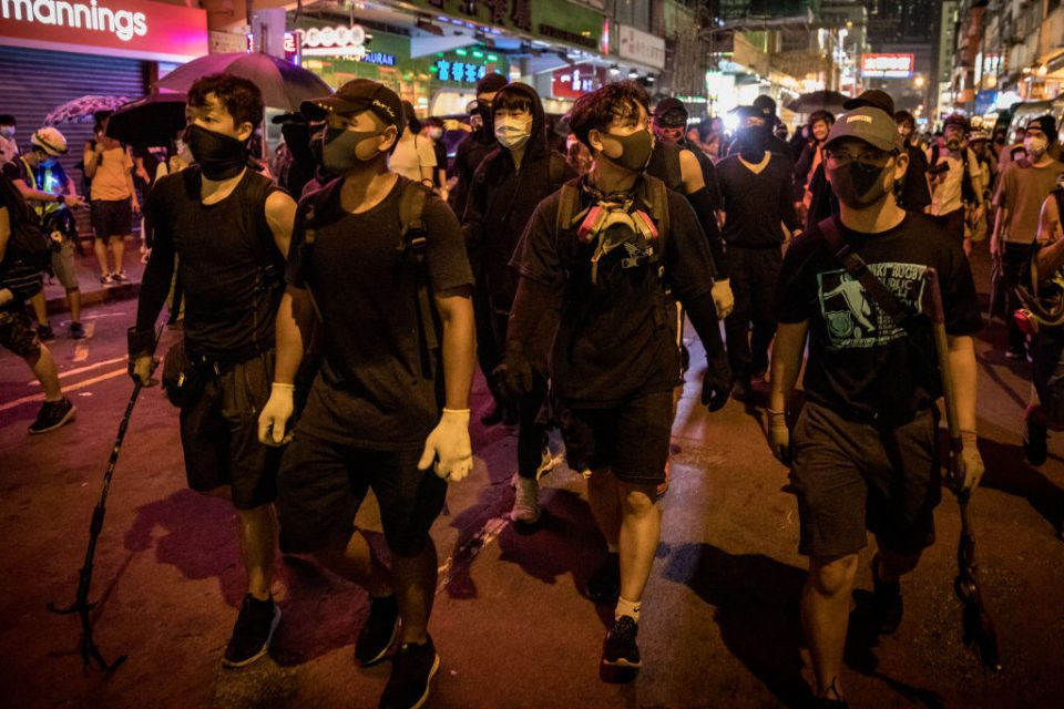 Hong Kong protesters walk down a city street in a pro-democracy demonstration