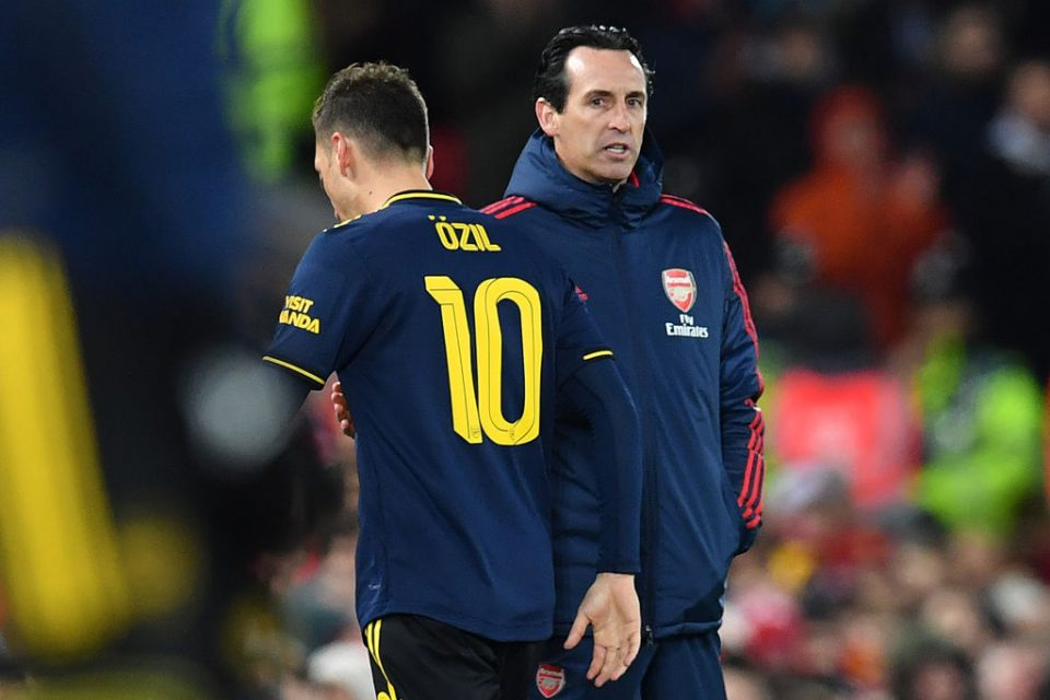 Arsenal's German midfielder Mesut Ozil (L) passes Arsenal's Spanish head coach Unai Emery as he leaves the pitch after being substituted off during the English League Cup fourth round football match between Liverpool and Arsenal at Anfield in Liverpool, north west England on October 30, 2019. (Photo by Paul ELLIS / AFP) / RESTRICTED TO EDITORIAL USE. No use with unauthorized audio, video, data, fixture lists, club/league logos or 'live' services. Online in-match use limited to 75 images, no video emulation. No use in betting, games or single club/league/player publications. /  (Photo by PAUL ELLIS/AFP via Getty Images)
