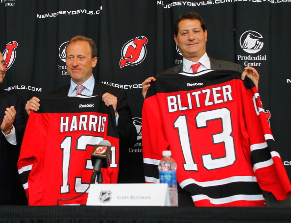 NEWARK, NJ - AUGUST 15:  Co-owners of the New Jersey Devils Joshua Harris (L) and David Blitzer pose for a photo with their jerseys during the press conference announcing the new ownership of the New Jersey Devils on August 15, 2013 in Newark, New Jersey.  (Photo by Andy Marlin/Getty Images)