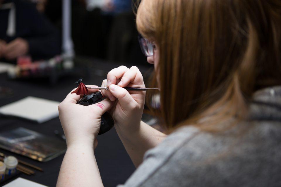 Games Workshop: Woman paints a miniature