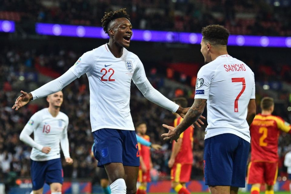 England's striker Tammy Abraham (L) celebrates with England's midfielder Jadon Sancho (R) after scoring their seventh goal during the UEFA Euro 2020 qualifying first round Group A football match between England and Montenegro at Wembley Stadium in London on November 14, 2019. - England won the game 7-0. (Photo by Glyn KIRK / AFP) / NOT FOR MARKETING OR ADVERTISING USE / RESTRICTED TO EDITORIAL USE (Photo by GLYN KIRK/AFP via Getty Images)