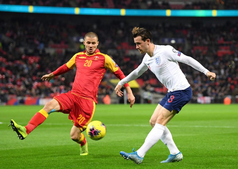 LONDON, ENGLAND - NOVEMBER 14: Ben Chilwell of England crosses under pressure from Aleksandar Sofranac of Montenegro during the UEFA Euro 2020 qualifier between England and Montenegro at Wembley Stadium on November 14, 2019 in London, England. (Photo by Michael Regan/Getty Images)