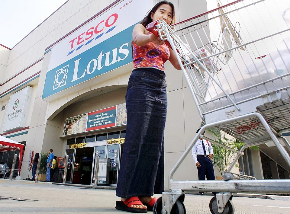 A Thai woman pushes a trolley past the entrance of