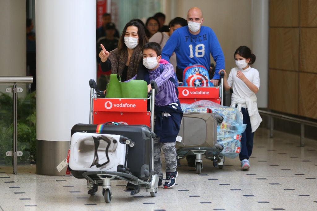 Australian citizens arrive from Wuhan wearing masks in a bid to slow the spread of the coronavirus