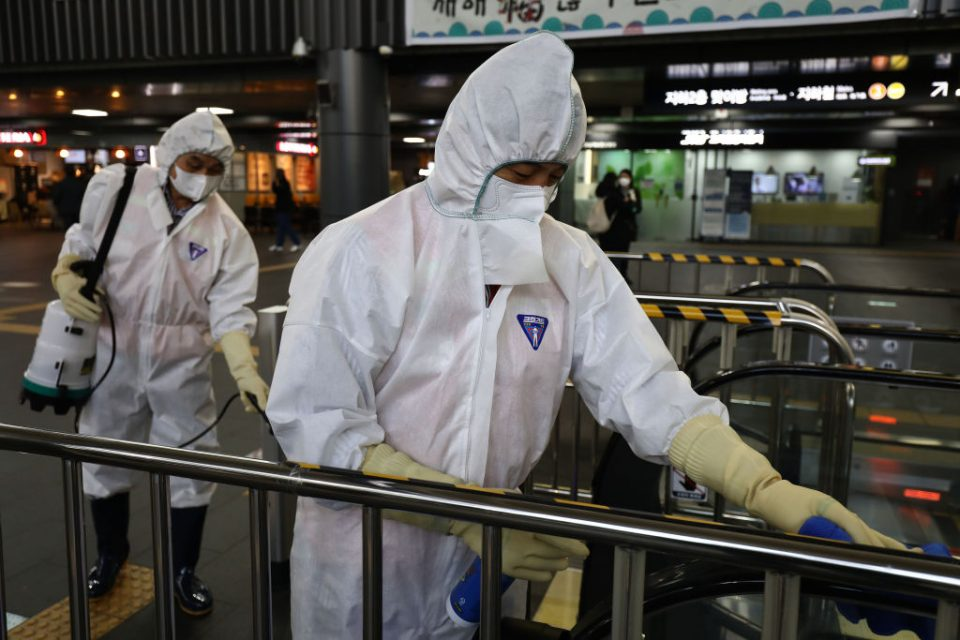 Coronavirus: Disinfection workers wearing protective gears spray antiseptic solution in an South Korean train terminal