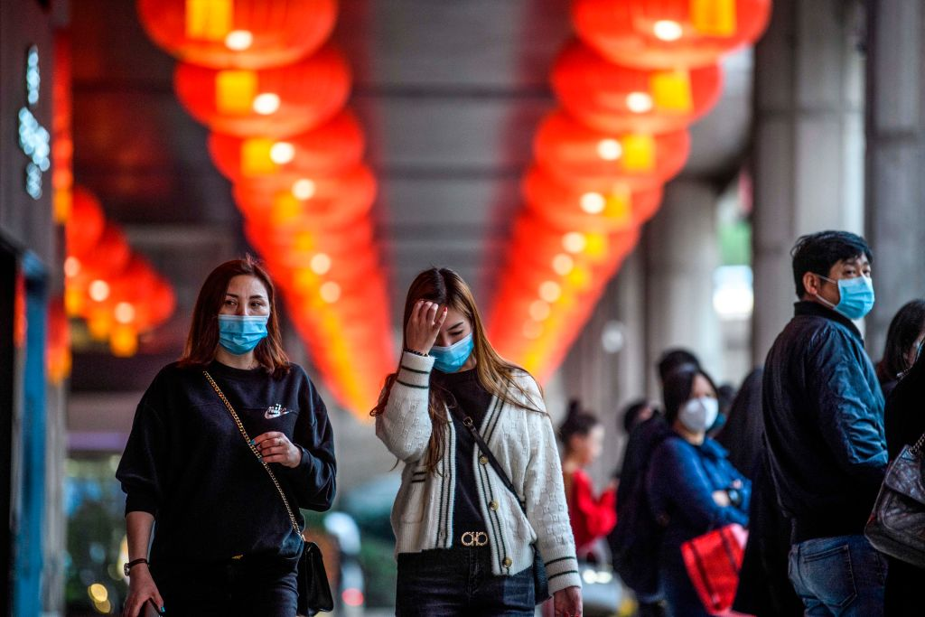 Pedestrians wear face masks as they walk outside the New Orient Landmark hotel in Macau amid the coronavirus outbreak