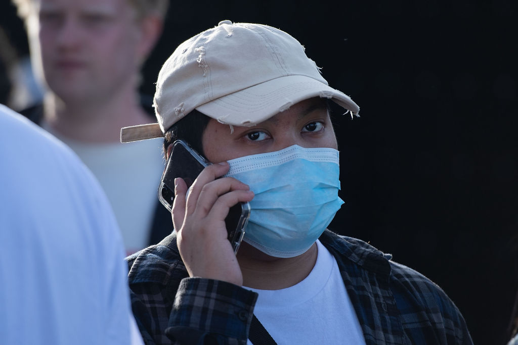 An Asian person wears a face mask to protect against the Covid-19 coronavirus