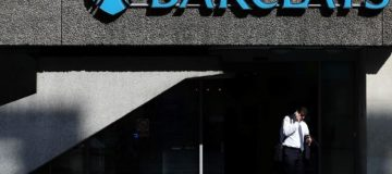Man stands outside a branch of Barclays bank