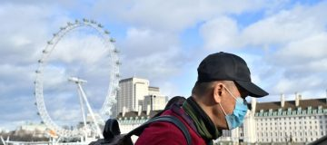 UK coronavirus: A man wears a face mask as he walks along the Thames embankment in central London