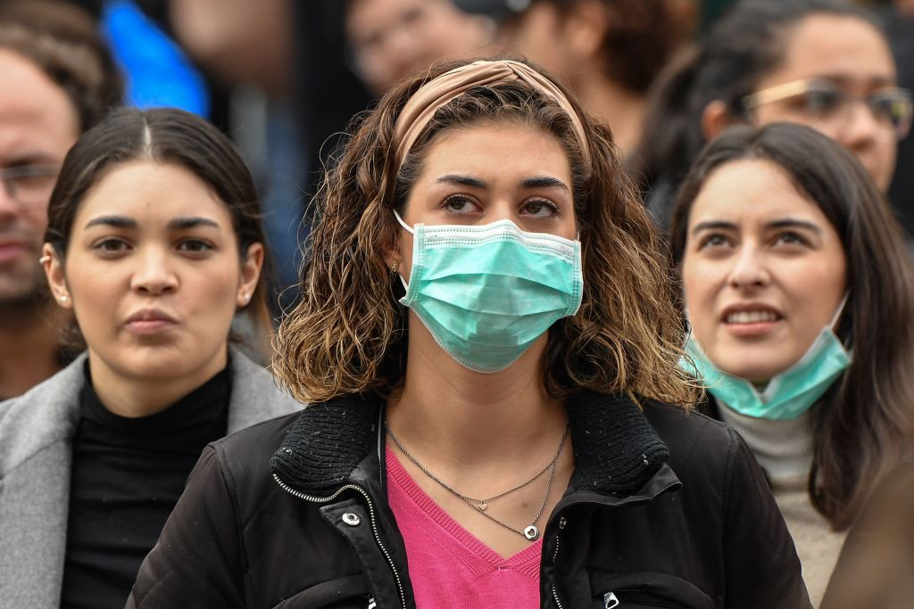 Tourist wearing protective respiratory masks wait near the Vatican amid the Italy lockdown over coronavirus