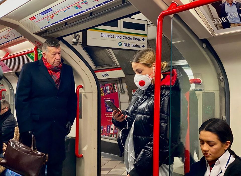 A woman wears a protective face mask against the coronavirus outbreak as she travels on a London tube train carriage at Bank Underground station