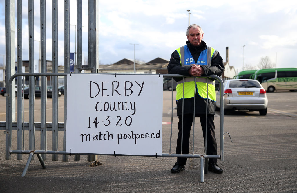A steward next to a postponement notice at Derby County