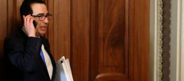 Treasury secretary Steven Mnuchin (centre) leaves the offices of Democrat Charles Schumer as the US rushes to finalise a $2 trillion coronavirus stimulus bill