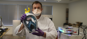 Alex Gibson of Edumaker holds up a coronavirus face mask his company and Cisco have 3D printed in response to NHS demand for PPE kit